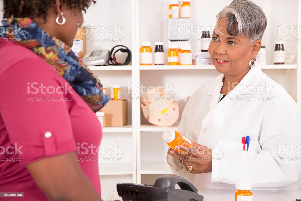 Pharmacist discusses prescription medication with customer at pharmacy. stock photo