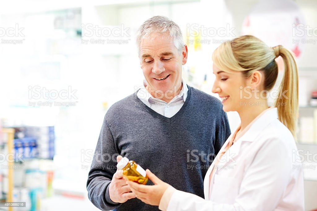 Pharmacist discussing over medicines with customer stock photo