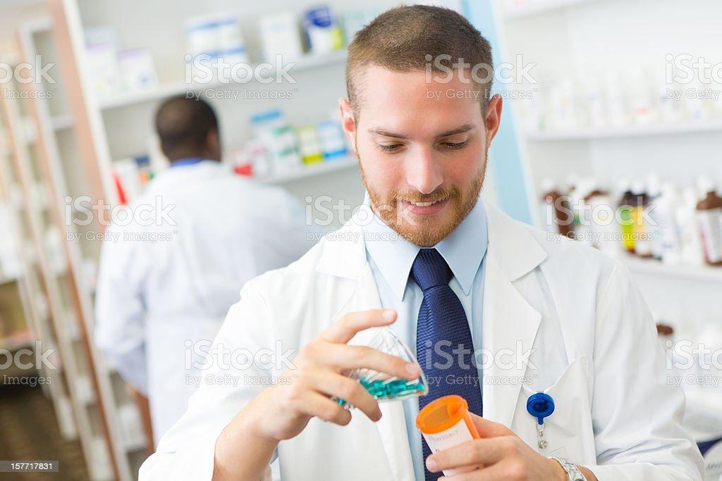 Pharmacist filling prescription medicine bottle at a pharmacy stock photo