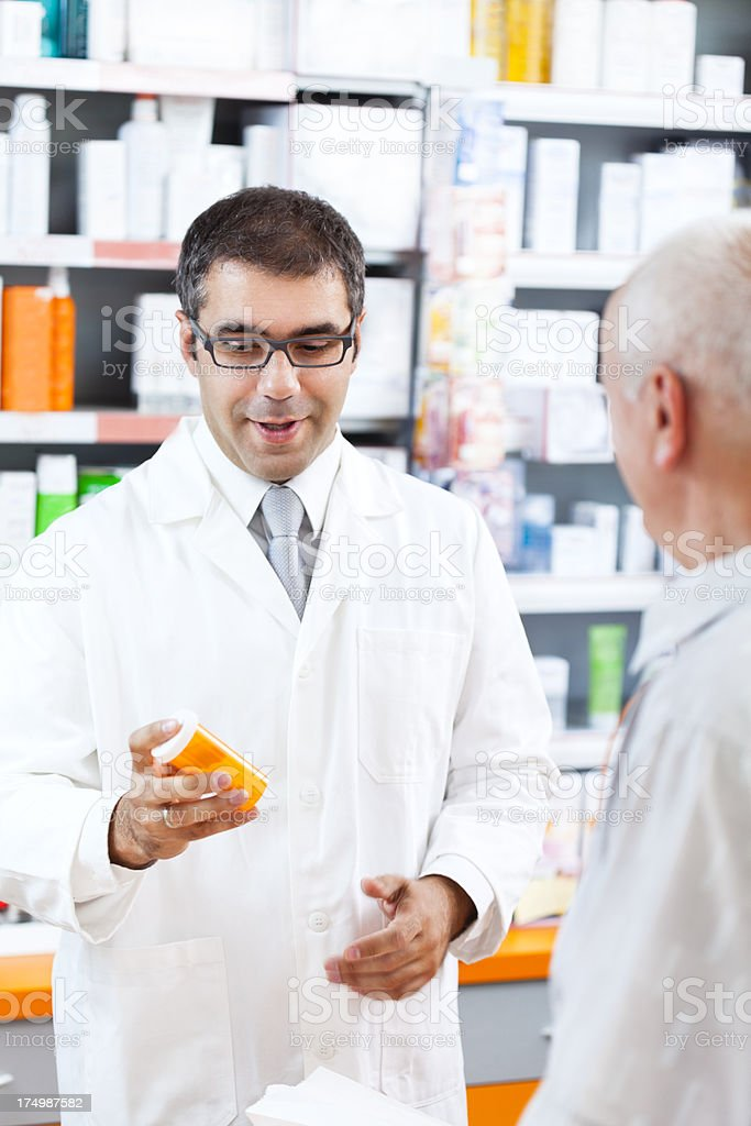 Pharmacist giving pill bottle to customer at the pharmacy royalty-free stock photo