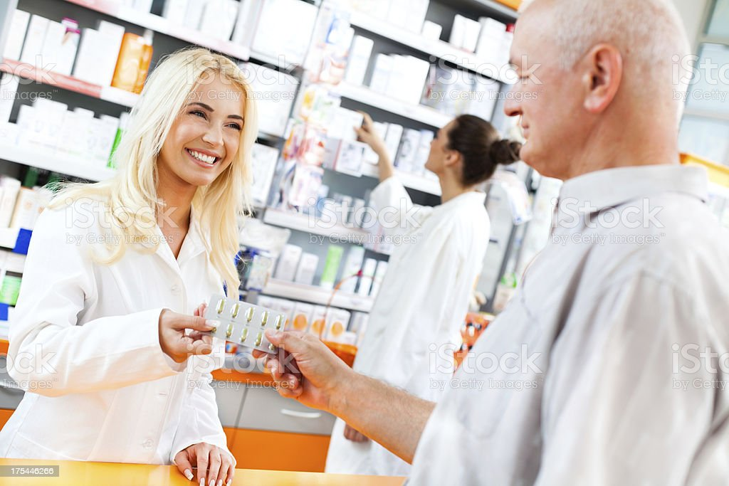 Pharmacist giving pills to a customer royalty-free stock photo