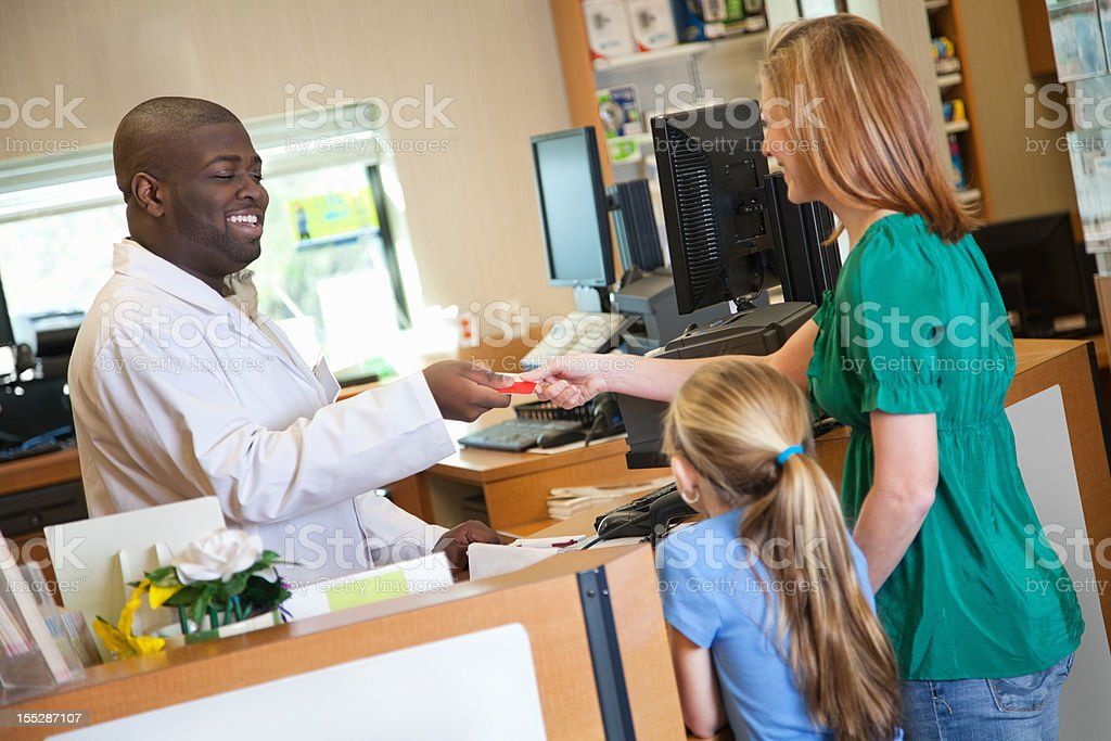 Pharmacist handing credit card back to customer royalty-free stock photo