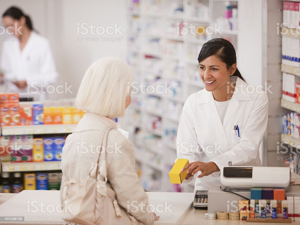 Pharmacist handing medication to customer in drug store stock photo