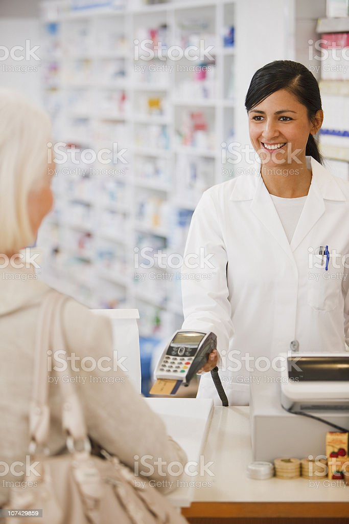 Pharmacist holding security device for customer in drug store royalty-free stock photo