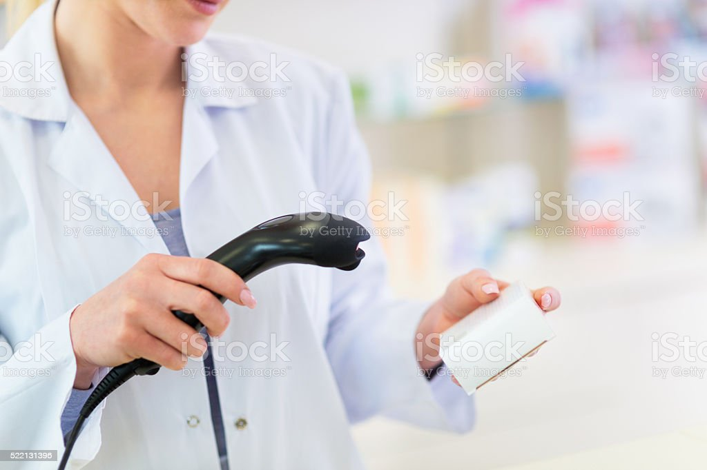 Pharmacist scanning product stock photo