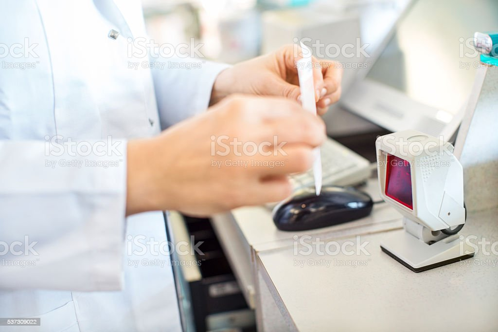 Pharmacist searching prescription medication in the database stock photo