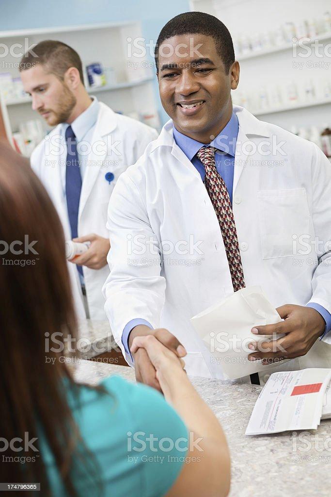 Pharmacist shaking hands with pharmacy customer royalty-free stock photo
