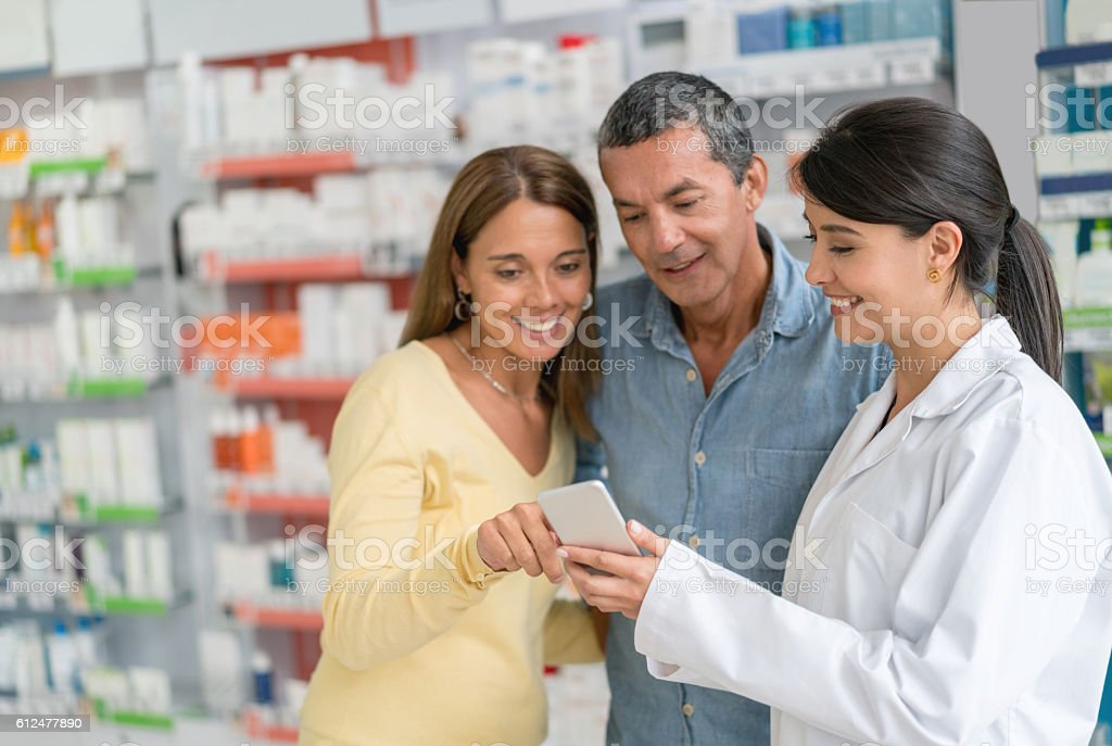 Pharmacist showing app to customers at a drugstore stock photo