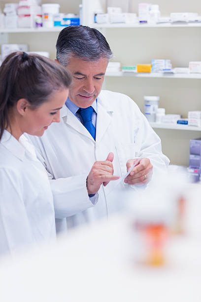 pharmacist speaking with his trainee about prescription stock photo - Pharmacist Trainee