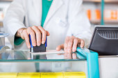 Pharmacist stamping prescription at desk