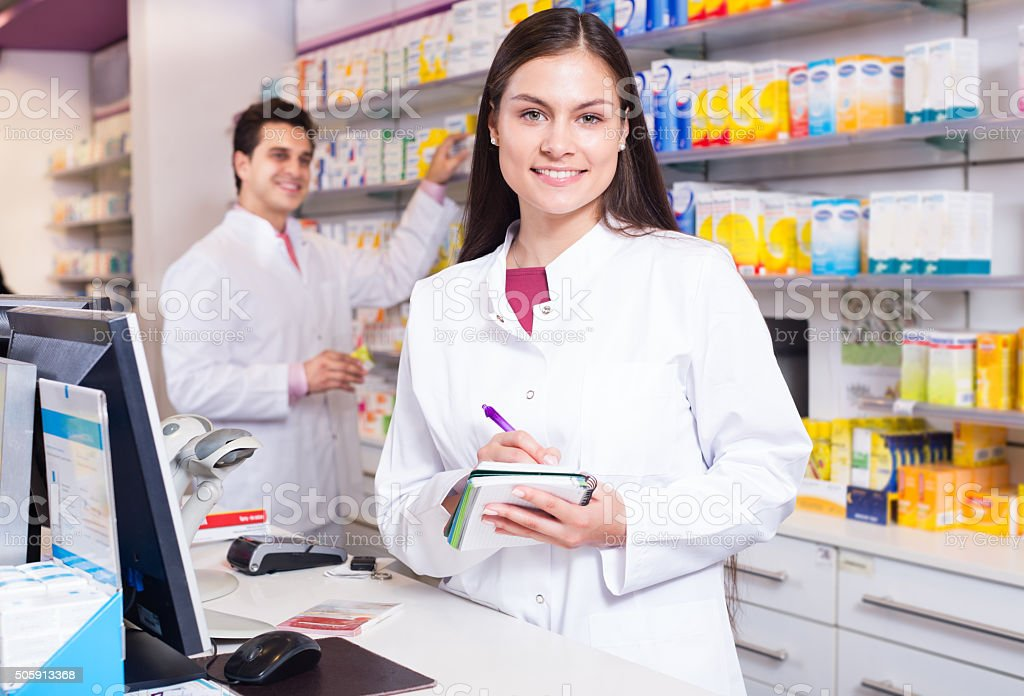 Pharmacist standing at pay desk stock photo
