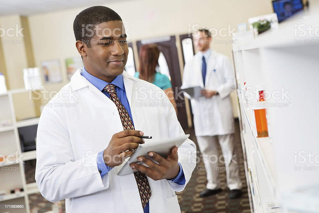 Pharmacist taking inventory of prescription medications on pharmacy shelves royalty-free stock photo