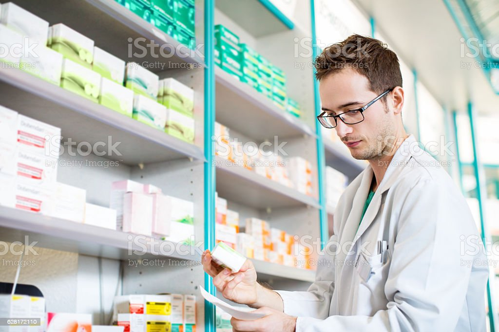 Pharmacist taking prescription medicine from shelf stock photo