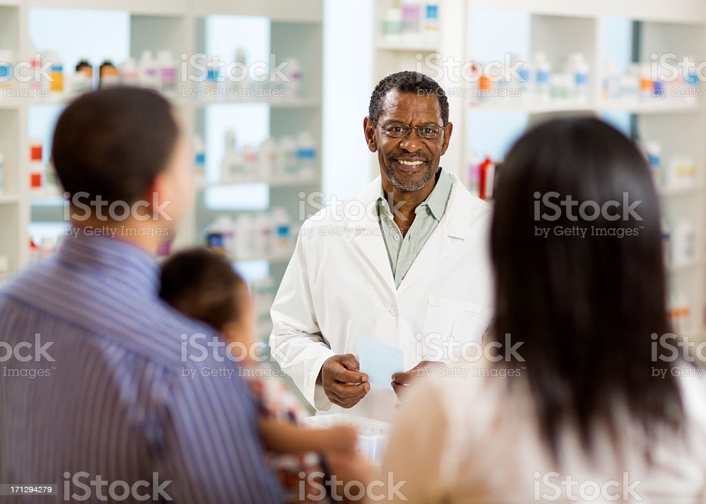 Pharmacist Talking to Young Family royalty-free stock photo
