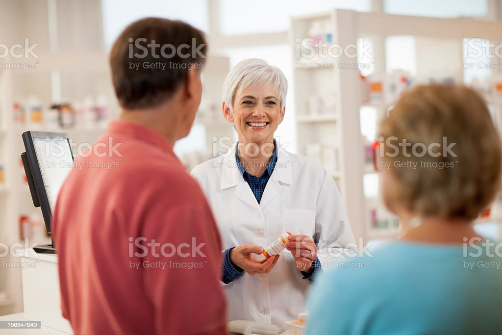 Pharmacist Talking with Adult Customers stock photo