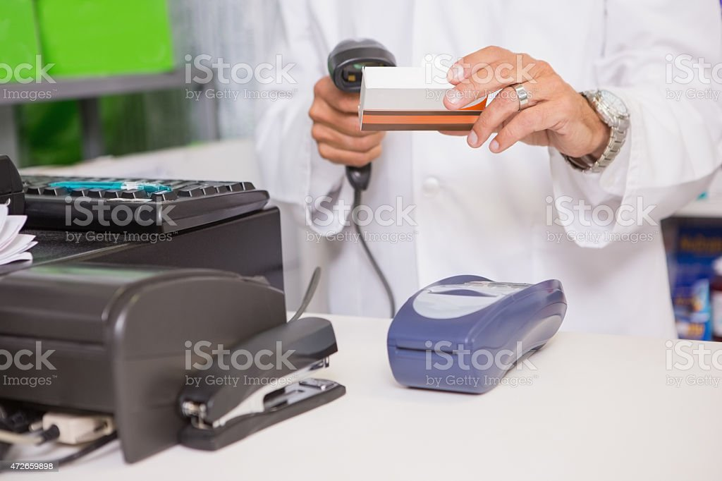 Pharmacist using machine and holding medicine stock photo