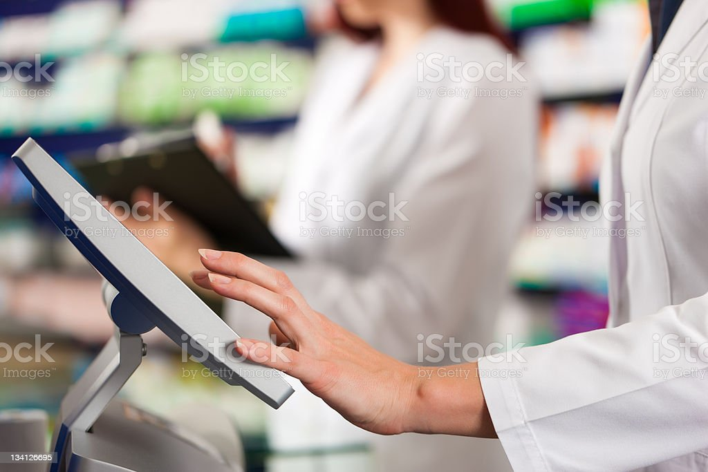 Pharmacist with assistant in pharmacy royalty-free stock photo
