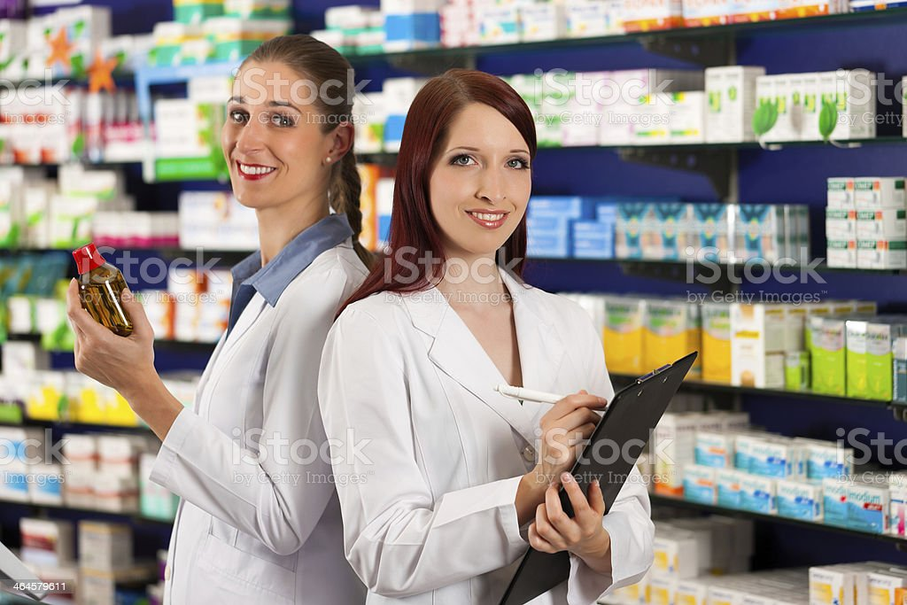 Pharmacist with assistant in pharmacy stock photo