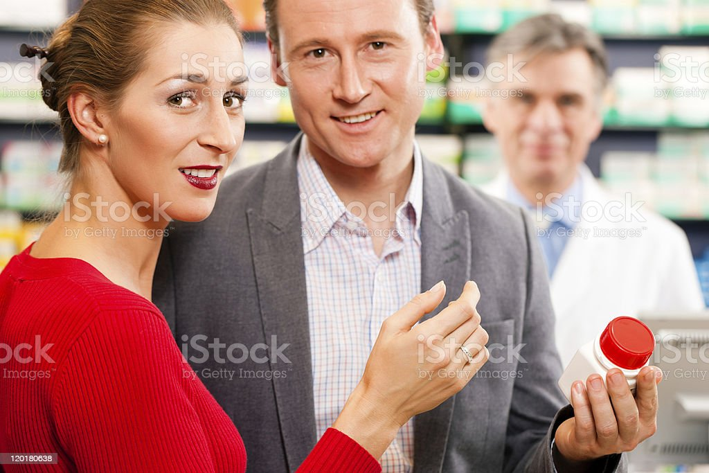Pharmacist with customers in pharmacy royalty-free stock photo