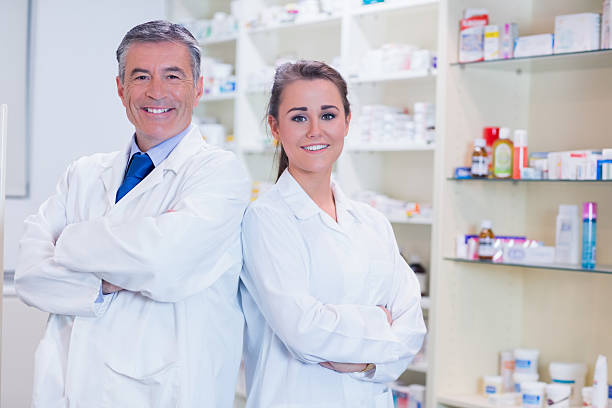pharmacist with his trainee standing stock photo - Pharmacist Trainee