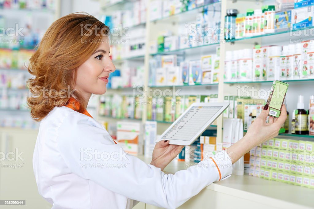 Pharmacist with tablet and drug stock photo