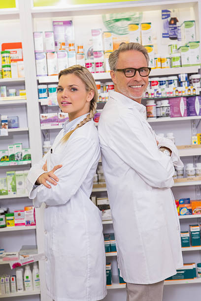 pharmacist with trainee standing with arms crossed stock photo - Pharmacist Trainee