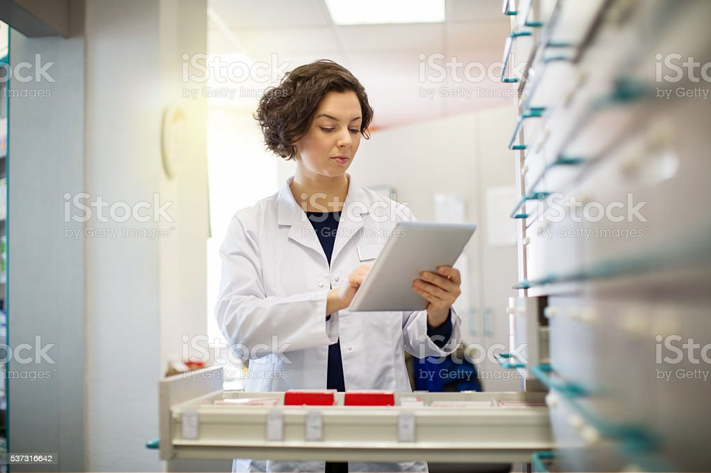 Pharmacist woman working on digital tablet stock photo