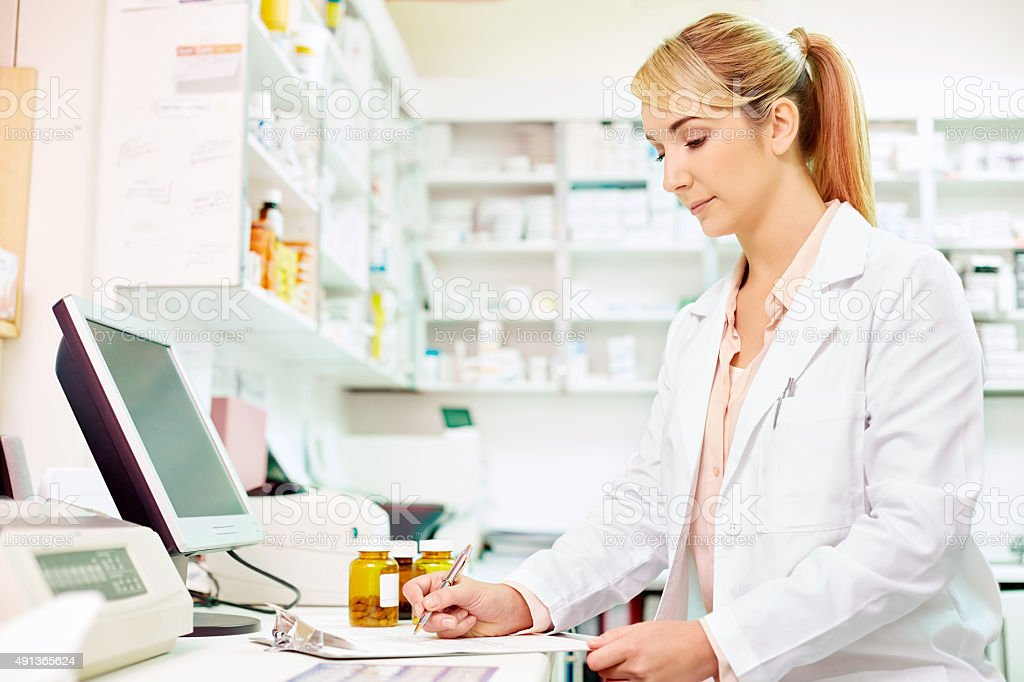 Pharmacist working at computer desk stock photo