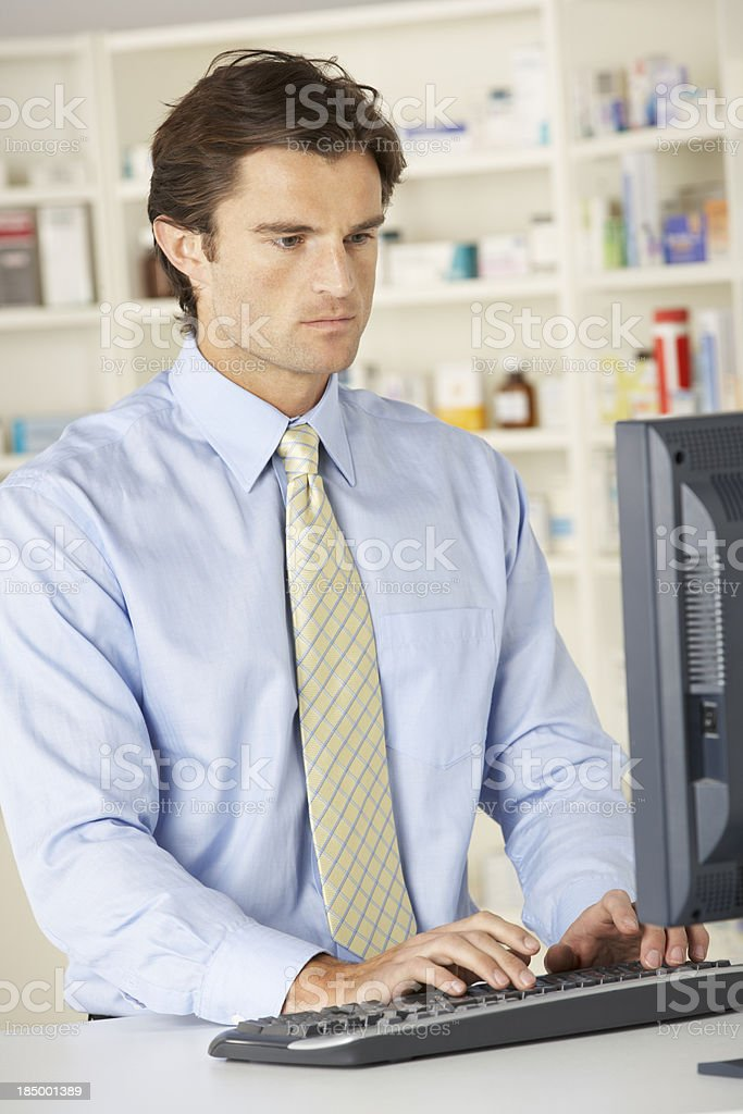 Pharmacist working on computer in pharmacy royalty-free stock photo