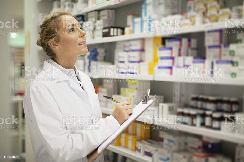 Pharmacist writing on clipboard stock photo