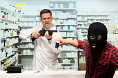 Pharmacists defending himself against robber