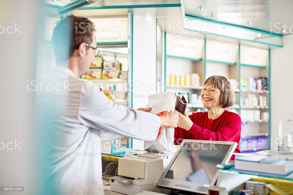 Pharmacist's giving prescription medication to customer stock photo