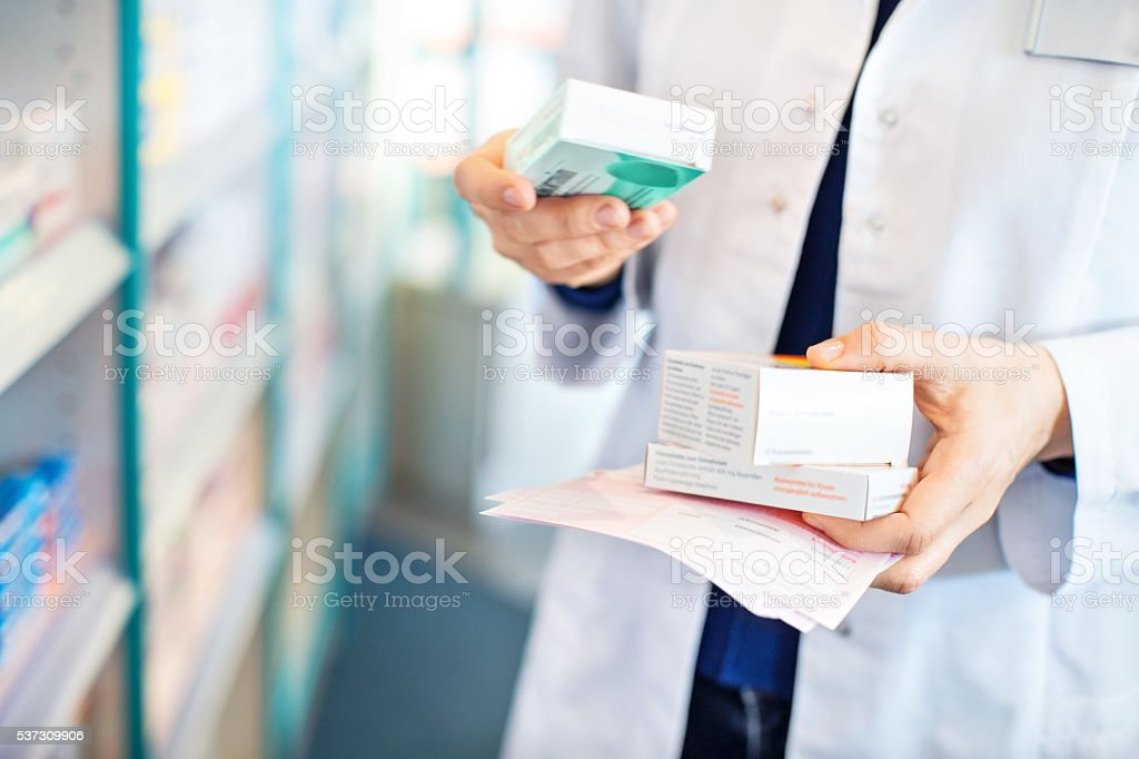 Pharmacist's hands taking medicines from shelf stock photo