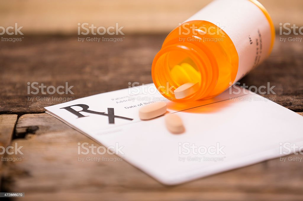 Pharmacy medication bottle with prescription pad. Pills spilling out. stock photo