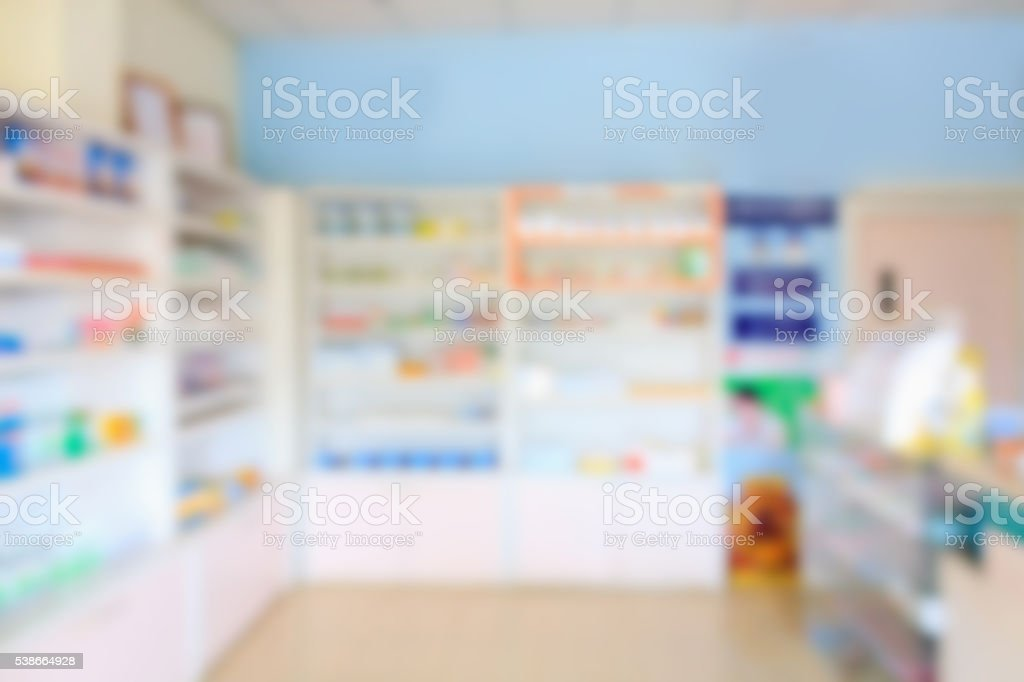 pharmacy shelves filled with medication blur background stock photo