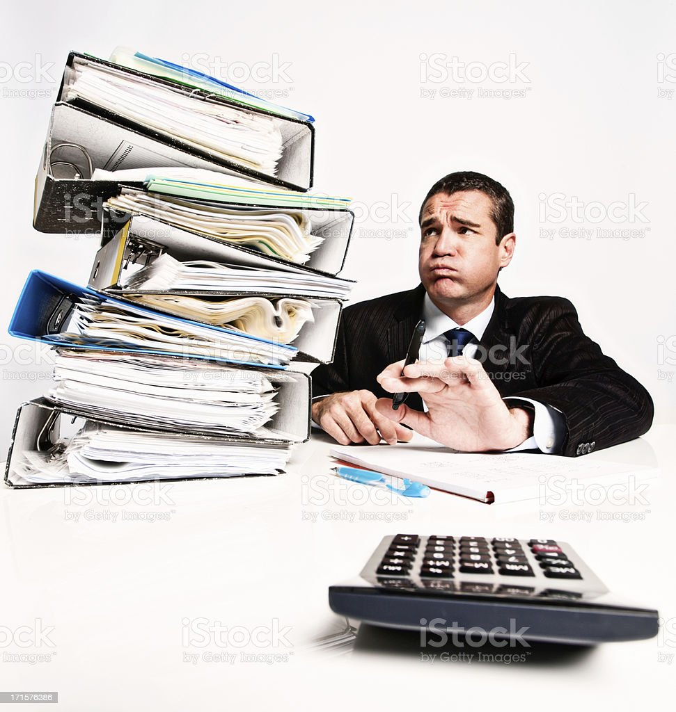 Phew! Worried businessman eyes enormous work pile nervously. royalty-free stock photo
