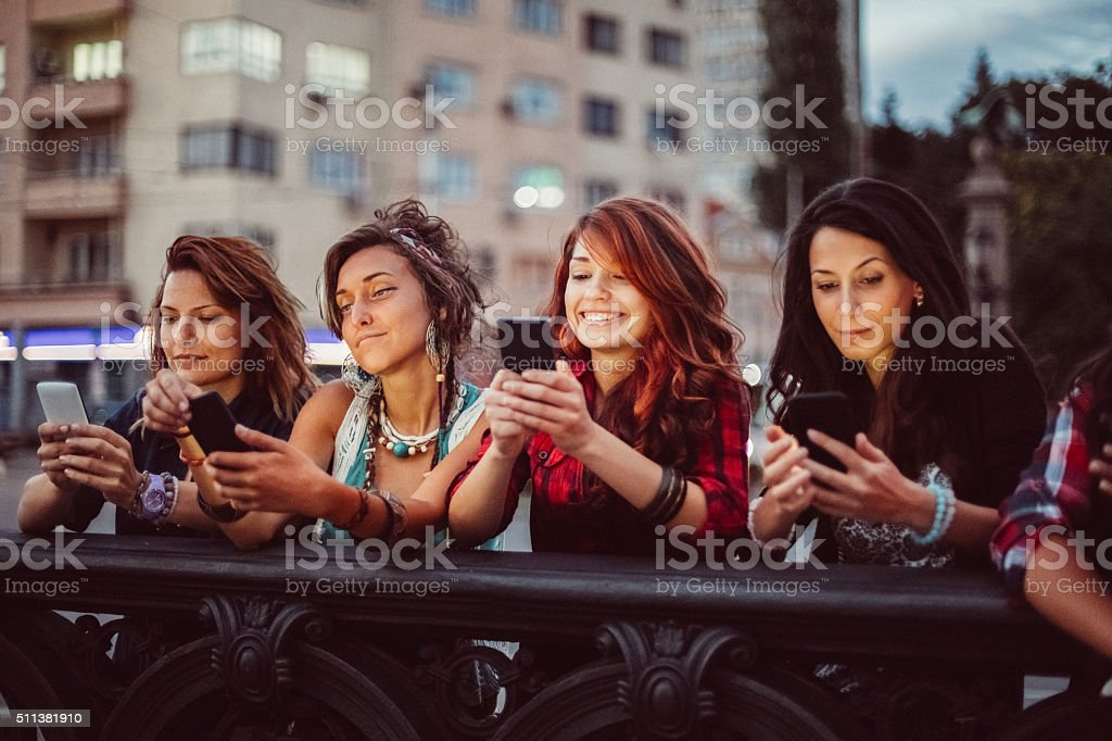 Phone addicted girls texting in the city stock photo