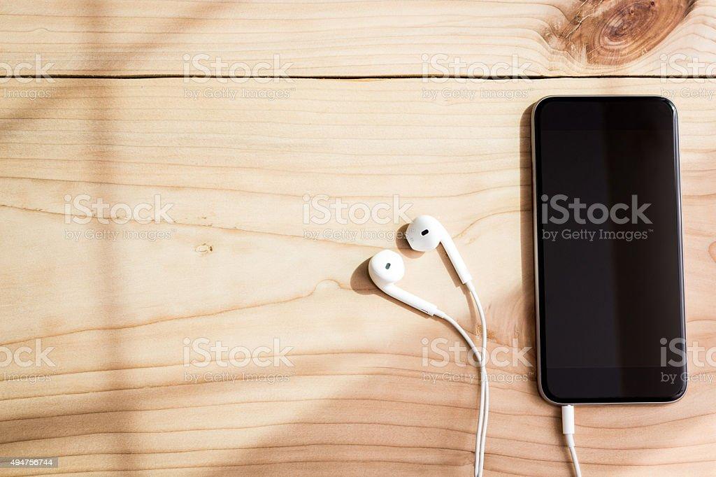 phone and headphone on wood background stock photo