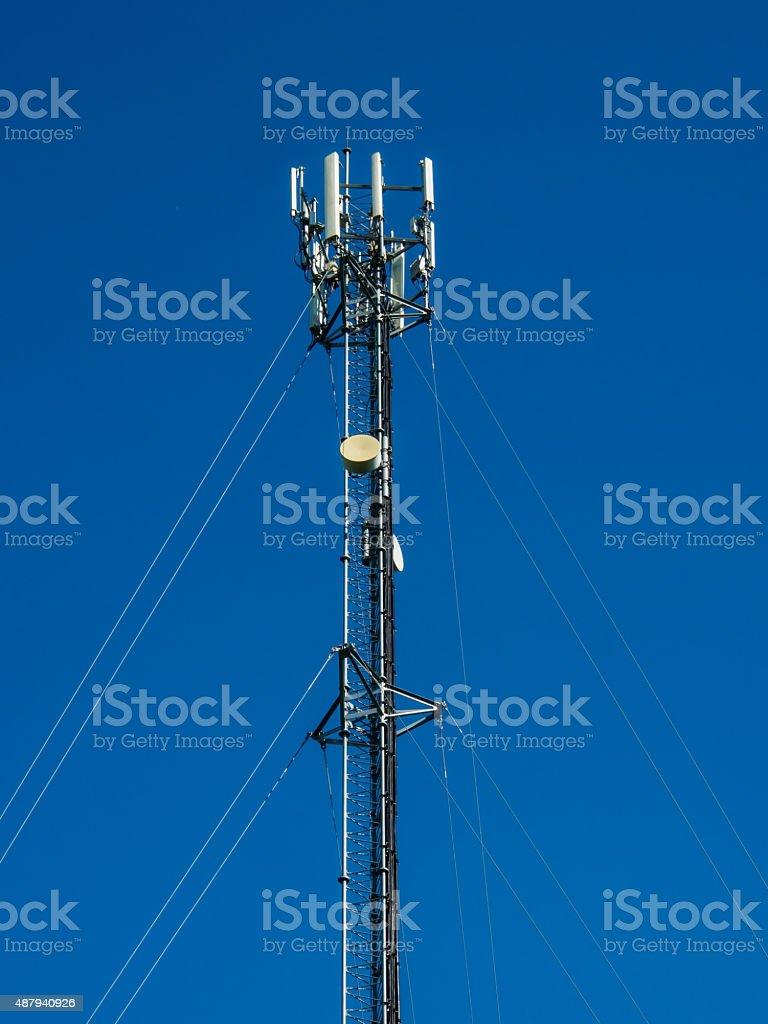 Phone antenna on blue sky. stock photo