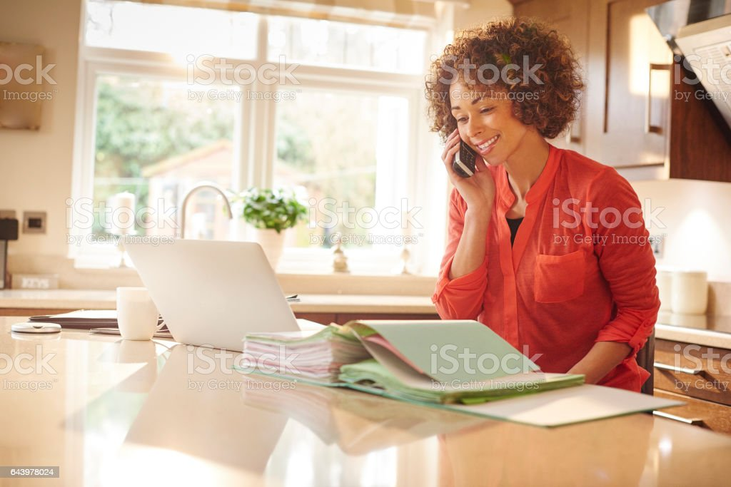 a woman sits in her kitchen and works through some paperwork whilst...