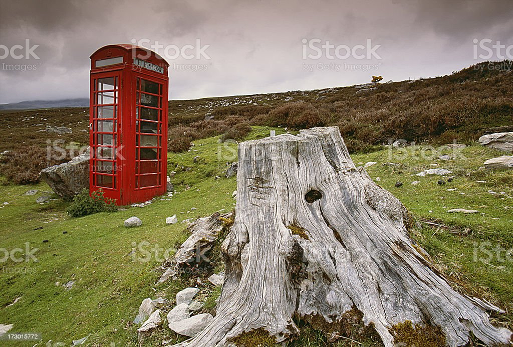 Phone box in rural scotland behind tree stump royalty-free stock photo