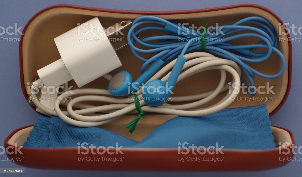 Phone charger & headphones stock photo