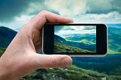 phone in a man's hand, mountain landscape photographs on