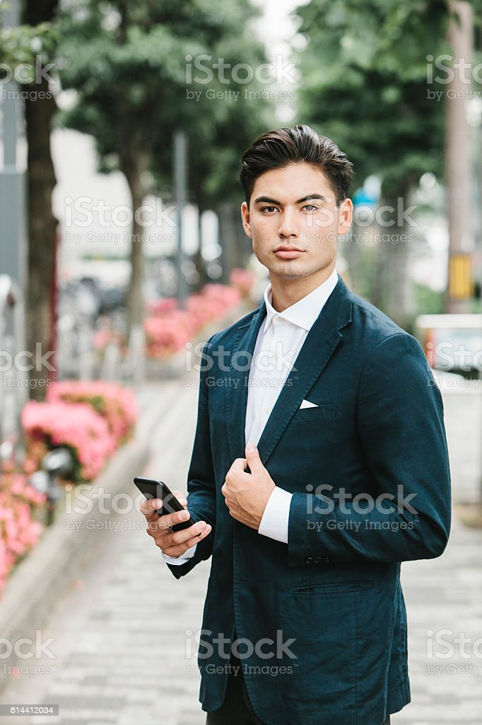Phone in the Hands of an Asian Businessman stock photo