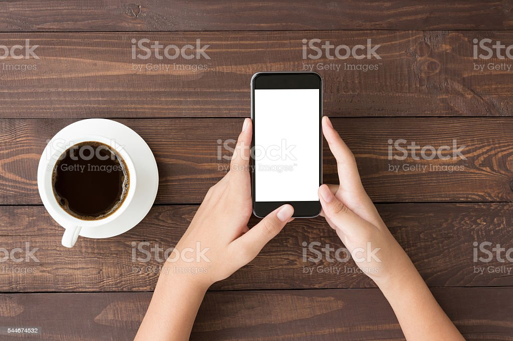 phone white screen in woman hand on table top view stock photo
