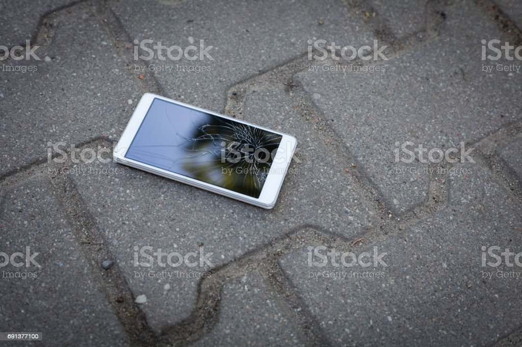 Phone with broken screen lying on the pavement stock photo