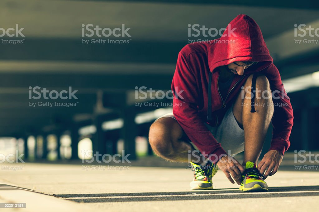Photo af an athletic man tying his shoelace stock photo