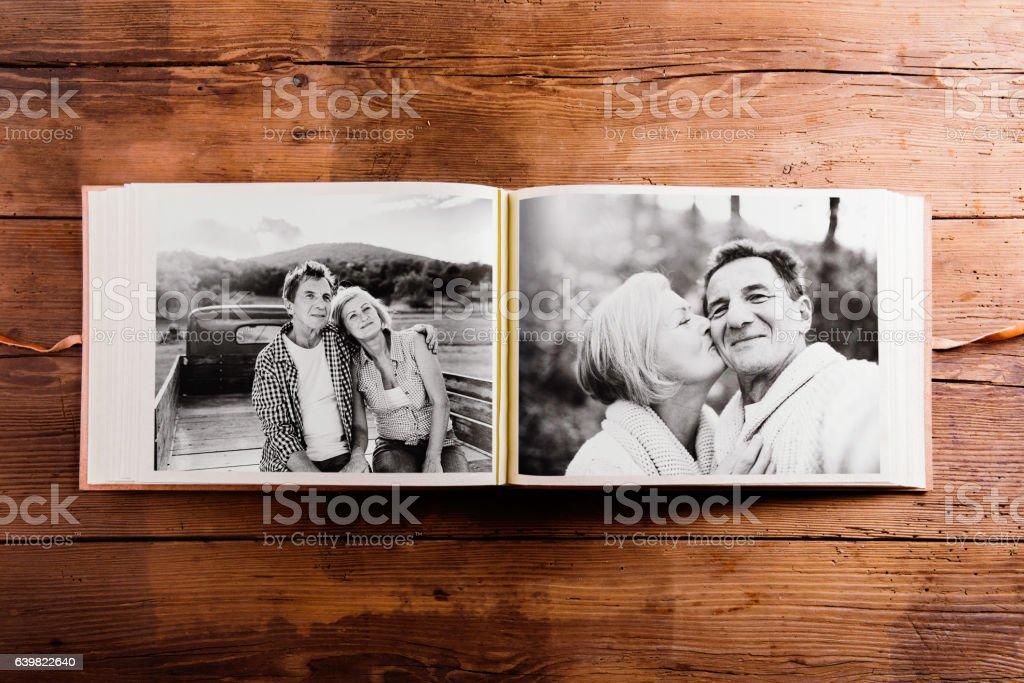 Photo album with black-and-white pictures of senior couple. stock photo