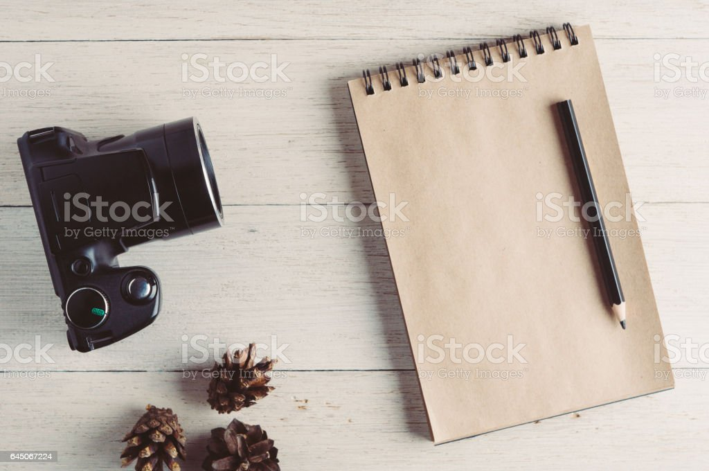 Photo camera and notebook on a white wooden background stock photo