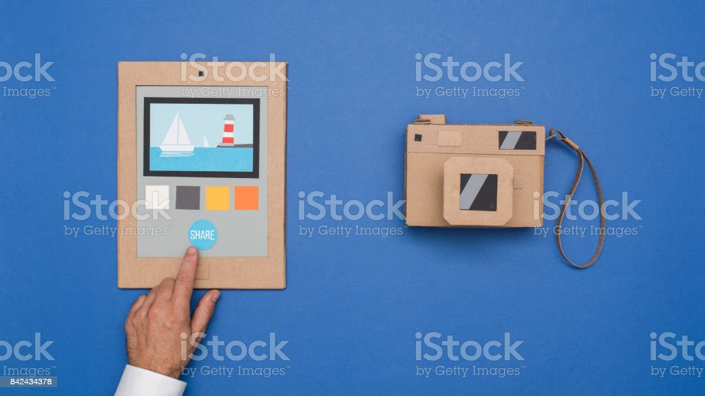 User editing photos on a cardboard tablet and handmade carton camera,...